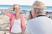 picture of take off clothes  - Happy casual man taking a photo of partner by the sea on a sunny day - JPG