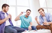 leisure, games, friendship, gambling and entertainment - three smiling male friends playing cards at home