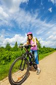 Smiling girl in pink helmet ready to ride a bike