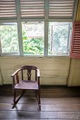 Isolated old rocking chair under several windows