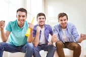 friendship, sports and entertainment concept - happy male friends with vuvuzela supporting football