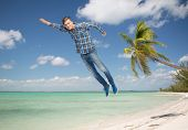 happiness, freedom, movement and people concept - smiling young man flying in air