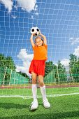 Girl holding football on both straight arms