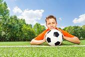 Happy boy holding football lays on green grass