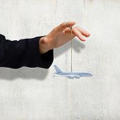 Close up of businessman hand holding airplane model on rope