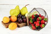 Ripe fruits and berries on table on wooden background
