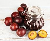 Tasty plum jam in jar and plums on wooden table on wooden background