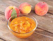 tasty peach jam with fresh peaches on wooden table