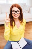 home, education, gesture and people concept - smiling teenage girl sitting on the floor with workboo