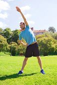 fitness, sport, training and lifestyle concept - smiling man stretching hand outdoors