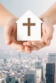 religion, christianity and charity concept - close up of woman hands holding paper house with christian cross symbol over city background