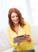 home, technology and internet concept - smiling teenage girl sitting on the couch with tablet pc com