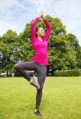 sport, exercise, yoga, park and lifestyle concept - smiling african american woman exercising outdoo