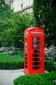 Red telephone booth in street with historical architecture in London.
