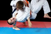 Strong sportsmen in  judogi are doing throws