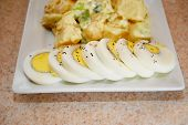 Sliced Egg With Potato Salad In The Background