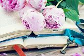 picture of bible story  - pile of vintage old books with pink  flowers and key stacked on table - JPG