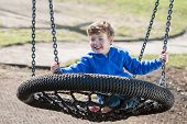 Boy Swinging on a Big Round Swing