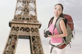 Happy smiling Asian young female backpacker with camera standing in front of Eiffel tower in Paris.