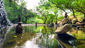 Zen garden. Meditate spiritual landscape of green forest with calm pond water and stone balance rock