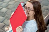 Young Beautiful Woman Reading Red Book In The City