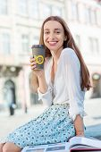 A Businesswoman With Cup Of Coffee To Go Against Sunny City Landscape