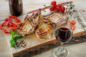 Pork Ribs Decorated With Cherry Tomatoes, Basil And Spices On Wooden Desk