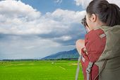 Asian female backpacker take photo in the countryside,