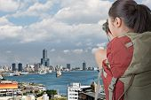 Asian female backpacker take photo in front of Kaohsiung harbor, Taiwan, Asia.