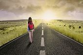 image of road trip  - Female college student walk on the road to start her journey and gain bright future - JPG