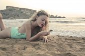 blonde girl at the beach writing on the phone