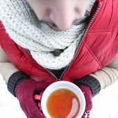 Man warming himself on a hot cup of tea in winter