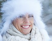 Smiling woman with white fur cap in winter snow