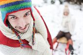 Man carrying woman in sled though snow in winter