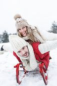 Happy couple on a sled together in winter in snow