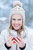 Smiling woman standing with black tea outdoors in winter