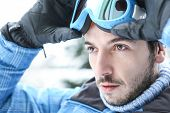 Man in ski holiday putting on his ski googles in winter
