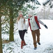 Happy smiling couple walking through snow in winter forest