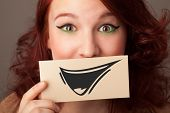 Happy cute girl holding paper with funny smiley drawing on gradient background