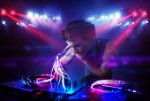 Handsome disc jockey playing music with light beam effects on stage