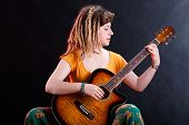 Young Girl With Dreadlocks Playing Guitar