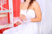 Bride in white dress and gloves holding decorative pillow with wedding rings, close-up, on bright ba