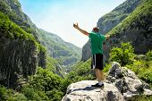 Man standing on stone and enjoying in beautiful nature - freedom concept