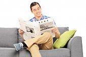 Peaceful young man reading the news seated on sofa isolated on white