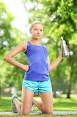 Female athlete holding a water bottle and resting after excericise, in a park