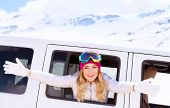 Portrait of cute cheerful woman with raised hands leaned out of the car window, goes to ski, enjoying winter vacation