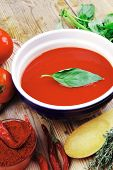 hot fresh diet tomato soup with basil thyme and dry pepper in big bowl on wood table