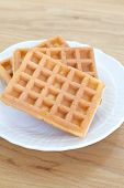 Delicious sweet waffle in ceramic white plate on wood table