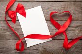 Photo frame or gift card with valentines heart shaped ribbon over wooden table background
