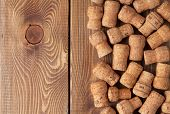 Champagne wine corks over wooden table texture background